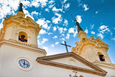 Facade of the Monastery of Fuensanta the patron saint of Murcia, Spain.  Built in 1694.  Showing the bells ringing for mass against a dramatic blue sky with clouds. Stock Photo