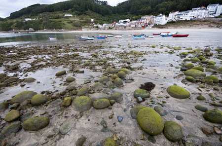 algal: Fishing village of Estaca de Bares, Galicia at the northernmost point of Spain   Algal covered rocks, fishing boats and beach at a low spring tide