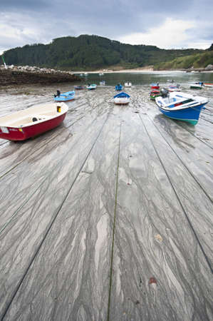 spring tide: The small harbour of the fishing village of Estaca de Bares, Galicia at the northernmost point of Spain  Fishing boats and beach at a low spring tide with the boats high and dry on the sand moored front and back