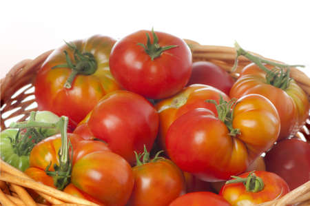 lycopene: Wicker basket of ripe red heirloom tomatoes isolated on white  Stock Photo