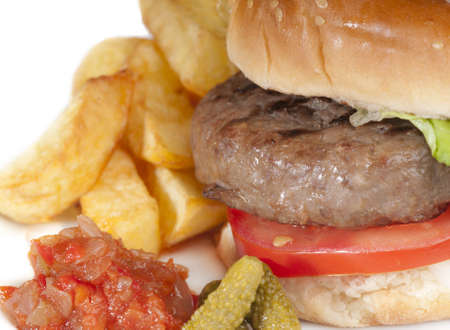 Simple home made basic hamburger with tomato slices, lettuce and onion in a white bread bun with chips and pickles. photo