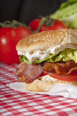 Bacon, lettuce and tomato sandwich or BLT freshly made, with vibrant, healthy colours on a red gingham tablecloth with whole tomatoes and lettuce in the backgound Stock Photo - 16868603