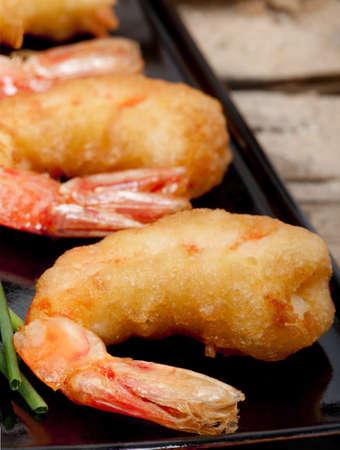 prepared shrimp: Closeup of three tempura deep fried prawns  on a black plate   Stock Photo