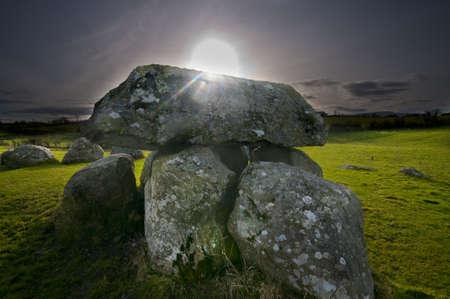 prehistoria: Vista espectacular de la puesta de sol sobre un sepulcro megal�tico y el c�rculo de piedra en la luz del atardecer de invierno Foto de archivo
