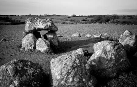 stoneage: Megalithic tomb and stone circle in the winter evening light  Black and white Stock Photo