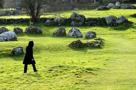 stoneage: Black figure walking past a stone circle in the winter evening light