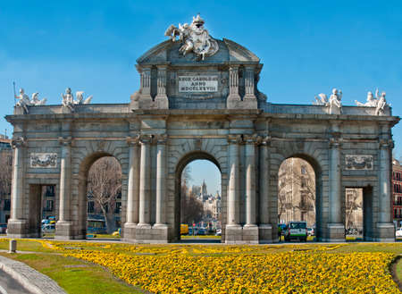 18th: Puerta de Alcal?, gateway to Madrid, Spain,  An 18th Centuary gate, originally in the City wall built by Francesco Sabatini commissioned  by Charles III.  Spring flowers , traffic and a blue sky.