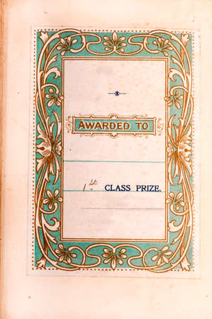 art nouveau frame: Printed insert dedicating a book as a first prize with an art nouveau style border on a pale green background.  About 100 years old.  Photo insitu in ton the first page of the book.
