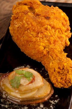buttery: Close up of one chicken drumstick, marinated in a chili sauce then deep fried in oatmeal batter, giving a thick, crunchy covering.  Served with a buttery fried potato stack on a black plate Stock Photo