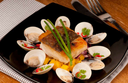 almejas: Seared cod fillet with crispy brown skin and accompanied by almejas, clams, yellow pepper and red onion.  garnished with red chili, coriander and chives.  On a black plate. Stock Photo
