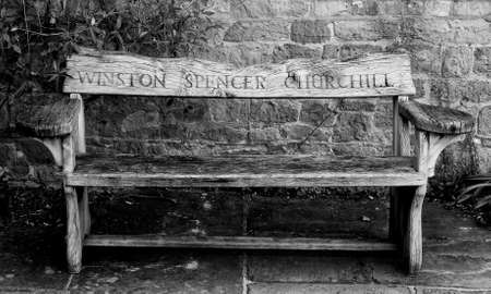 flagging: Wooden garden bench with the name Winston Spencer Churchill carved in the back from Chartwell House, Kent, his home until he died in 1965.  Afgainst a stone wall on stone flagging.  Black and white . Editorial