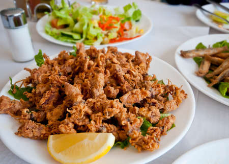 calamares: Spanish tapa of deep fried tiny squid, chopitos, garnished with a lemon slice.  Salad and fried sardines in the background.
