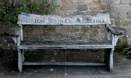 flagging: Wooden garden bench with the name Winston Spencer Churchill carved in the back from Chartwell House, Kent, his home until he died in 1965.  Afgainst a stone wall on stone flagging.