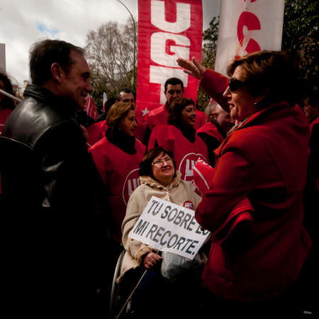 MADRID SPAIN - MARCH 10: Demonstration taking place in central Madrid against the cuts in education, social benefits, salaries and health that have been imposed as  solutions to the economic crisis.  Lady in a wheelchair with a sign , your bonus is  my cu