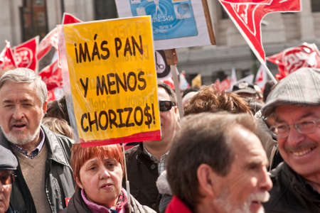 chorizos: MADRID SPAIN - MARCH 10: Demonstration taking place in central Madrid against the cuts in education, social benefits, salaries and health that have been imposed as  solutions to the economic crisis.  The sign reads more bread and less chorizos (crooks) Editorial