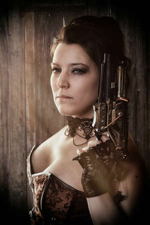 a woman in steam punk outfit holding a gun and looking into the camera in front of a wooden  photo