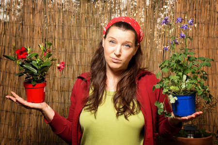 headgear: Woman gardening and holding two flower pots with different plants in front of a bamboo fence unable to choose one