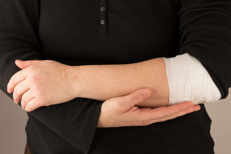 elbow brace: Bodypart showing arms  - holding a bandaged arm