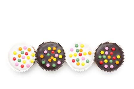 little cakes with chocolate lentils in a row against white background photo