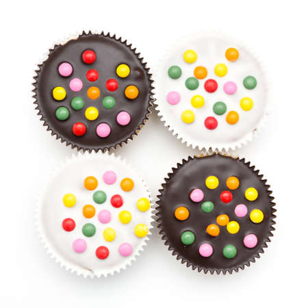 sinful: little cakes with chocolate lentils in a sqaure against white background