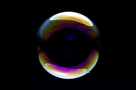 single colorful soap bubble against black background
