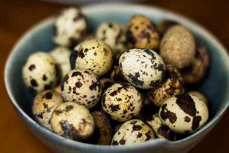 huevos de codorniz: pequeños huevos de codorniz en un tazón azul Foto de archivo