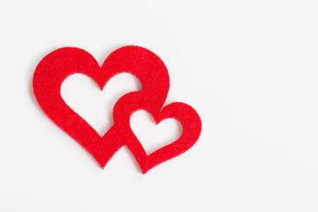 two hearts together: two red hearts of felt come together against white background Stock Photo