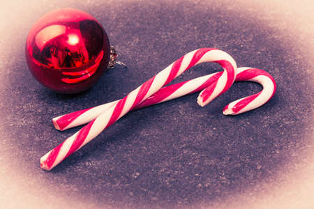 grundge: two christmas candys and balls on a dark underground in vintage and grundge style
