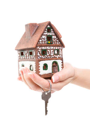 heritage protection: female hand hold a little house and a key in the hand Stock Photo