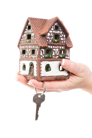 female hand hold a little house and a key in the hand photo