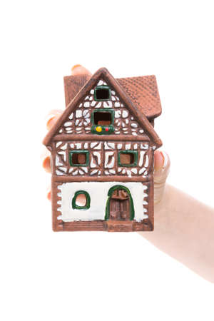heritage protection: female hand holding a little house against white