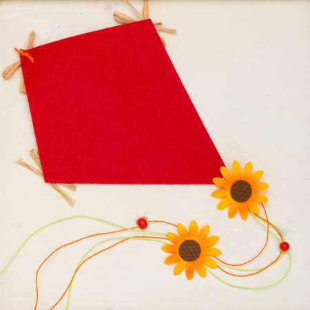 Homemade paper kite in white wooden picture frame