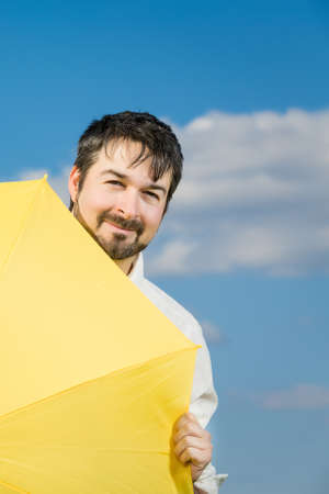 closing time: man with a yellow umbrella against blue sky