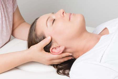 massage: femme allongée reçoit un traitement à la tête