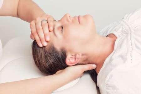 dolor de cabeza: mujer acostada recibe tratamiento en la cabeza