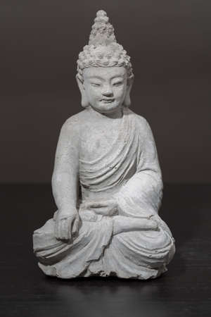 orte: grey stone buddha with stones against white background Stock Photo