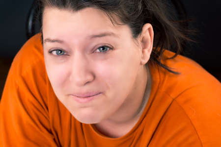 portrait of a woman who is crying wearing a orange shirt Stock Photo