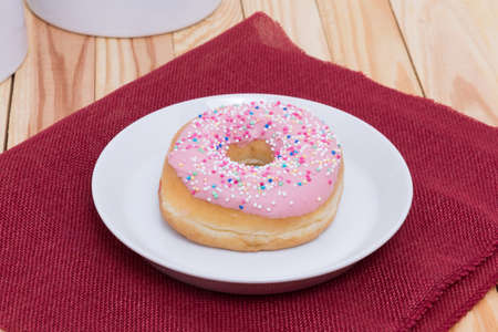 sinful: sweet delicious pink donut with colorful sprinkles Stock Photo