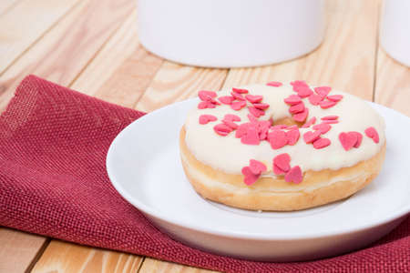 sinful: sweet tasty donut with white glaze red sugar  hearts and red heart for decoration Stock Photo