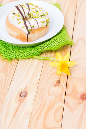 sinful: sweet delicious donut with white icing and pistachios