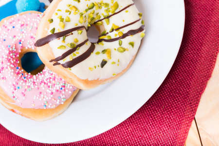 sinful: a selection of four tasty donuts on a plate Stock Photo