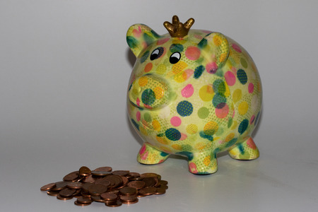 view at a piggy bank with a heap of coins on a white background Stok Fotoğraf