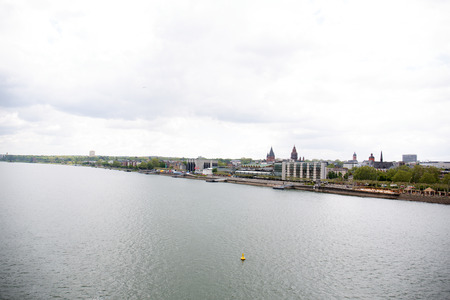 Distant view on a riverbank at the rhine river from the mainz bridge germany photographed on a cloudy day