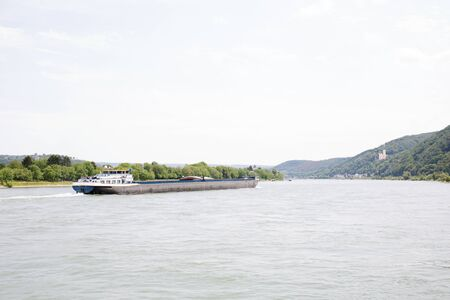 View on a container ship on the rhine river in Koblenz. Rhine and surrounding photographed during a sunny day