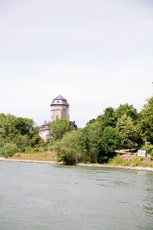View on a tower surrounded by trees in Koblenz. Rhine and surrounding photographed during a sunny day Imagens