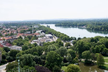 View from the tower of the new civil hall on the sea and the tree area in Hanover germany photographed during a walk at a cloudy sunny day