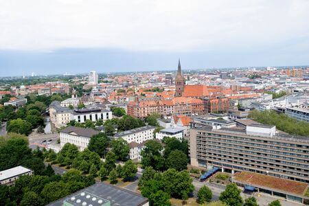 Distant view from the tower of the new civil hall in hannover germany and the steeple photographed during a walk at a cloudy sunny day