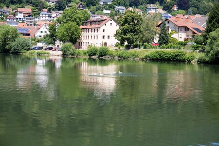 View on houses reflecting on the Neckar river in Heidelberg. Germany. Photographed during a tour by ship on the Neckar in Germany Imagens