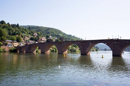 View on a bridge and a natural hill under blue skies at the neckar in Heidelberg germany photographed during a tour by ship on the neckar in germany