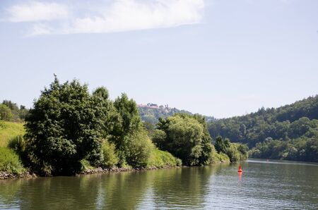 View on a natural hill under blue skies at the neckar in Heidelberg germany photographed during a tour by ship on the neckar in germany